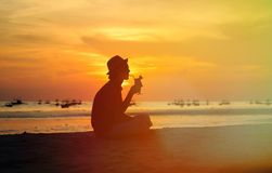 Silhouette of young man drinking cocktail at Royalty Free Stock Photography
