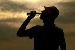 Silhouette of young man drinking water in summer Stock Images