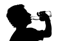 Silhouette of young man drinking water Stock Photos