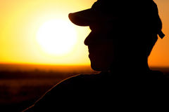 Silhouette of a young man in a field at sunset Stock Photography