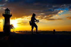 Silhouette of the young man fishing near the beach Stock Photography