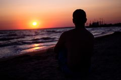 Silhouette of a man who sits on the sand near the sea, in the rays of the setting sun near the sea. place under the text, relax on. Silhouette of a young man royalty free stock photography