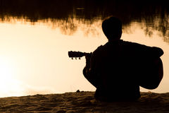Silhouette of a young man with a guitar Royalty Free Stock Image