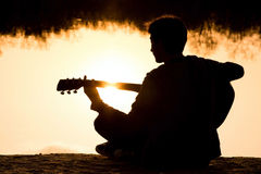 Silhouette of a young man with a guitar Royalty Free Stock Photos