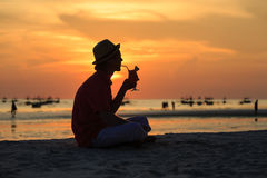 Silhouette of young man having drink at sunset Stock Images