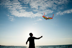 Silhouette of young man holding a kite flying in a blue sky with clouds at sunset Royalty Free Stock Photo
