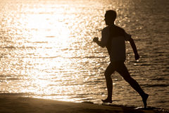 Silhouette of young man jogging at seashore Royalty Free Stock Image