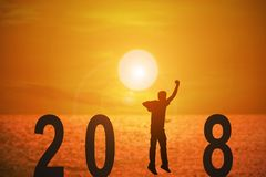 2018 news year. Silhouette of young man jumping on the beach between 2018 years with beautiful sunset at the sea, concepts of news year and business target Royalty Free Stock Photography