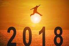 2018 news year and concepts for business and target. Silhouette of young man jumping over the numbers 2018 years with beautiful sunset at the sea, concepts of royalty free illustration