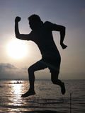 Silhouette of young man jumping. Stock Images