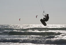 Silhouette of Young Man Kite Boarding in sea Waves. Silhouette of Young Man Kite Boarding in the sea royalty free stock photo