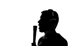 Silhouette of a young man listening to music with headphones Stock Images