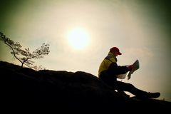 Silhouette of young man looking at a map in nature while hiking Royalty Free Stock Images