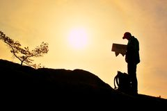 Silhouette of young man looking at a map in nature while hiking Stock Image