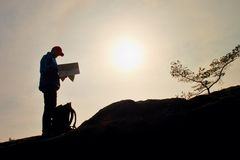 Silhouette of young man looking at a map in nature while hiking Stock Photos