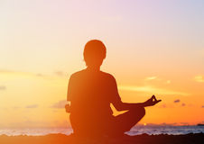 Silhouette of young man meditating at sunset Stock Photos