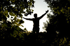 Silhouette Young Man Opening his Arms at the Field Stock Image