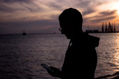 Silhouette of a young man with a phone in hands on the background of a beautiful sunset sky by the sea. Silhouette of a young man in a sports hoodie with a hood royalty free stock photo