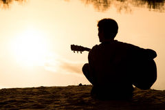 Silhouette of a young man  playing guitar sitting on the sand Royalty Free Stock Photo