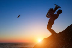 Silhouette of a young man playing the trumpet on rocky sea coast during amazing sunset. Royalty Free Stock Image