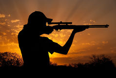 Silhouette of a young man with ponytail shooting Stock Photo