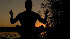 Silhouette of young man practicing yoga on the beach at sunset. 4K