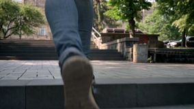 Silhouette of young man is running on stairs in park in daytime in summer, hurrying concept.  stock footage