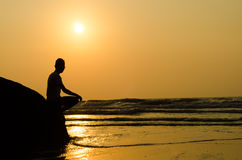 Silhouette of young man sitting on the edge of rock Stock Images