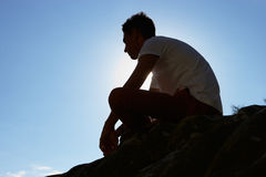 Silhouette Of Young Man Sitting On Rock Stock Photo