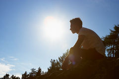 Silhouette Of Young Man Sitting On Rock Royalty Free Stock Photos