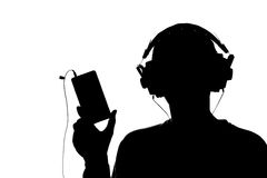Silhouette of a young man with a smartphone with headphones Royalty Free Stock Images