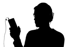 Silhouette of a young man with a smartphone with headphones Stock Photos