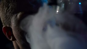 Silhouette of a young man Smoking a hookah in the dark, slow motion. Close-up. Close-up of a man Smoking a hookah on a black background stock footage