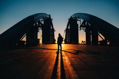 Silhouette of young man standing at the bridge Stock Photography