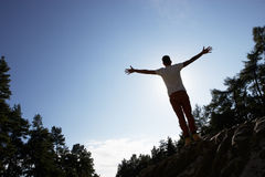 Silhouette Of Young Man Standing On Rock Royalty Free Stock Images