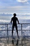 Silhouette of young man standing at the seaside Royalty Free Stock Images