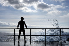 Silhouette of young man standing at the seaside Stock Photo