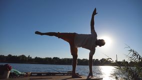 Silhouette of young man standing at yoga pose on a wooden jetty at lake. Sporty guy training at nature. Athlete doing. Exercise outdoor. Sunlight at background stock video
