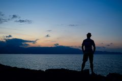 Silhouette of young man at sunset on coast Stock Photography