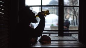 Silhouette of a young man who is drinking beer and eating snacks at the bar by the window. stock video