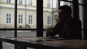 Silhouette of a young man who drinking coffee in a cozy cafe. stock video