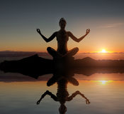 Silhouette of a young meditating lady Stock Photography