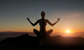 Silhouette of a young meditating woman Royalty Free Stock Photos