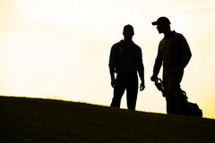 Silhouette of young men standing in golf course with trolley Royalty Free Stock Photos