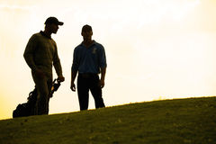 Silhouette of young men standing in golf course with trolley Stock Photo