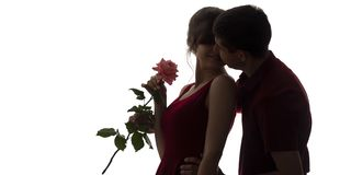 Silhouette of a young man and woman fall in love on white isolated background, boy came up behind to girl to make a surprise with stock photos