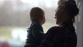 Silhouette of a young mother with her baby. A young woman carefully holds her child and looks out the window. Waiting. For Dad stock footage
