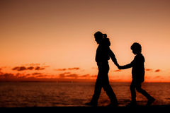 Silhouette of a young mother and her son walking Royalty Free Stock Photos