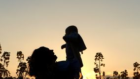 Silhouette of mother throws baby into sky. Newborn son have fun in field. stock footage
