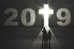 Parents and children with number 2019. Silhouette of young parents with their children standing near a shining door shaped a crucifix with numbers 2019 stock photo